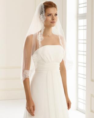 Braut im Brautkleid trägt Schleier mit Spitze