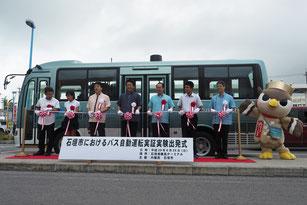 自動運転バス運行実験の出発式で記念撮影する関係者=25日午後、石垣港離島ターミナル