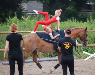 Die beiden Voltigiererinnen turnen gemeinsam, während die Longenführerin das Pferd longiert.
