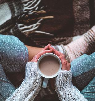 Frau mit Kaffee am Boden sitzend, ganz gemütlich
