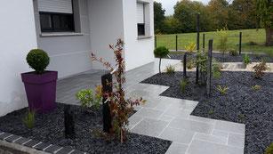 Entrée de maison en dalles naturelles et massif sur paillage minéral: ardoise et gravillon gris blancs ocre
