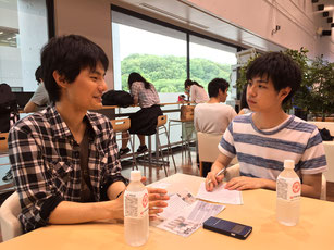 Sugano (left) speaks during his interview with Uchino at the cafeteria