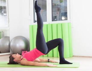 Junges Mädchen im Sportdress streckt die Beine während einer Übung