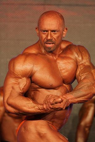 Bodybuilder mit abslout extremer Muskelmasse posiert
