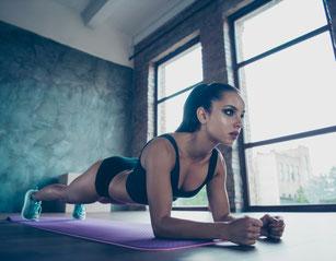 Frau liegt auf einer Matte und treibt Sport