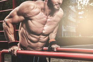 Training eines muskulösen Mannesmit an einem Reck