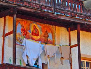 ein grell leuchtendes Wandbild unter einem alten Balkon