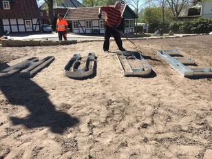 Auf einem noch unbewachsenen Teil des Dorfplatzes legen ehrenamtlich tätige Dorfverein-Mitglieder den Hüde Schriftzug an.
