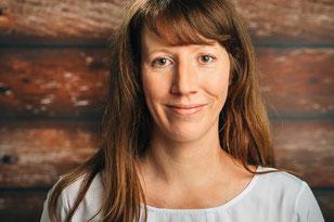 Portrait Jana Scheidemann: schaut direkt in die Kamera, lächelt leicht, die rotbraunen Haare fallen auf einer Seite locker über die Schulter.