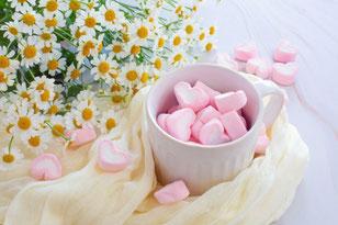 水色に白の水玉模様のカップ&ソーサ。赤いバラの花が一輪添えられている。