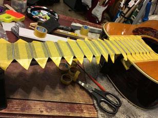 指板に黄色いマスキングテープを貼り、ギターネックの指板を磨く作業の準備