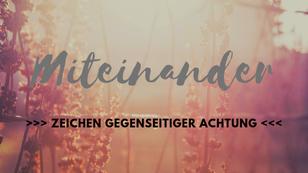 """Hier ist ein Bild mit Spruch zu sehen: """"Miteinander - als Zeichen gegenseitiger Achtung"""". Im Hintergrund sind Blumendolden von Wildblumen, die durch Sonnenschein nur schemenhaft zu sehen sind."""
