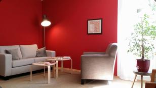 Wartezimmer der Heilpraxis mit Couch, Tischchen und Sessel