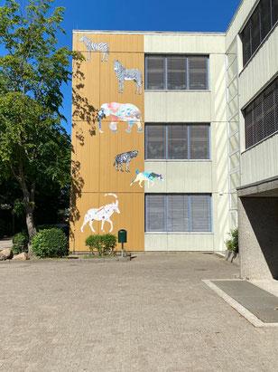Verschiedene übergroße Bilder von phantasievoll colorierten afrikanischen Wildtieren an den Gebäuden der Grundschule Alfred-Faust-Straße in Bremen-Kattenesch, Bremen Obervieland (Foto: 05-2020, Jens Schmidt)