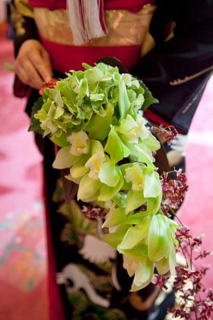 グリーンのシンビジウムと茶系のランで流れる様な和装ブーケ