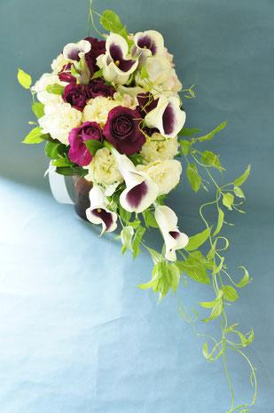 カラーとディープパープルのバラがメイン花材のクラッチキャスケード