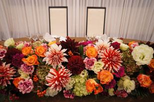 結婚式 ウェディング メインテーブル 高砂 赤やオレンジのお花で秋のイメージ