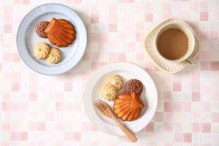 パンジーの活けられたガラス瓶。チョコチップのマドレーヌが並んだ皿。コーヒーの入ったカップ&ソーサ。