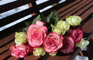 ベンチに置かれたバラの花束