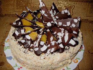 Бисквит с масляным кремом, фруктами и шоколадом в кокосовых хлопьях
