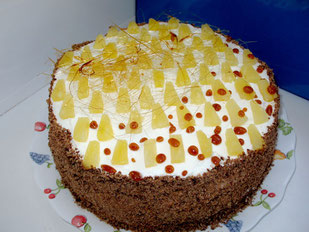Бисквит с ананасами внутри и сливками, украшенный карамельными нитями и кусочками ананаса