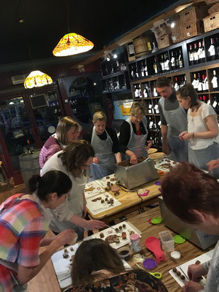 Attendees enjoying making their chocolates, before sitting down to enjoy cheese and biscuits, learn about how chocolate is made and try some chocolate.