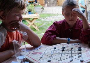 Kinder beim Brettspiel Alquerque zum Kindergeburtstag