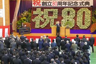 田本徹さんの指揮で、80年前に制作された開校記念歌を斉唱する参列者ら=20日午後、八重農