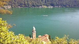 tief unten liegt die Kirche Santa Maria del Sasso vor dem smaragdgrünem Wasser des Lago