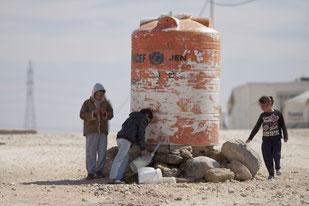 Niños llenando garrafas de agua en el campamento de Al-Zaatari, Jordania / Mustafa Bader