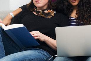 photo de deux jeunes filles assises devant un livre et un ordinateur