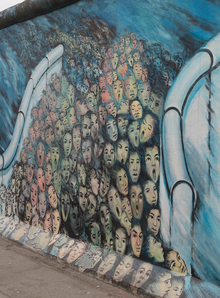 One of the artworks at the East Side Gallery in Berlin: a flood of people breaks through the Berlliner Wall