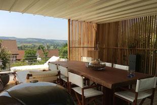 Hausgarten, moderne Gartengestaltung mit Gräserbepflanzung im Vordergund. Sitzplatz mit Korbsesseln und weißem Sonnenschirm