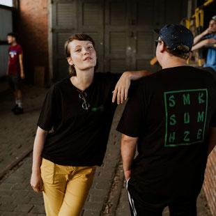 Eine Frau lehtn an einem Mann und beide tragen ein schwarzes T-Shirt mit der Aufschrift SMK SUM HZE