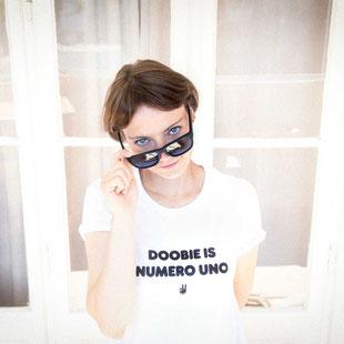 """Eine Frau trägt ein weißes T-Shirt mit dem Aufdruck """"Doobie is numero uno"""""""