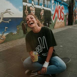 Eine Frau trägt ein grünes T-Shirt mit einem weißen Peacezeichen und sitzt auf einem Skateboard