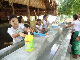 植林活動の後、新設した手洗い場で手を洗う子どもたち(カンサト小学校)