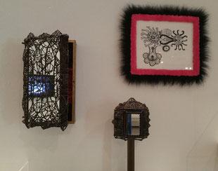 3 sculpturen van Ferdina Jansen, . Een klein spiegelkastje, met een smeedijzeren traliewerk ervoor. Een soort doosje op een standaard, geheel omkleed met dicht smeedwerk. Een smeedwerkje in gelijst in zwart en roze bont.