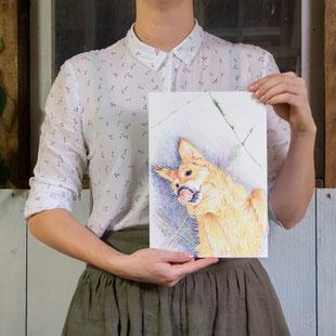 Vrouw houdt tekening van een hond vast op A4 formaat.