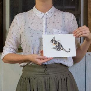Vrouw houdt tekening van een kat vast op A5 formaat.