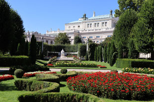 Colourful garden of Vienna, with flourishing flowers, a marble statue and an impressive building in the back.