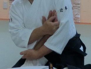 ④左手を陰の陽で受けの上腕屈側に当てそれを介して丹田に結ぶ。上体は左胸と共に受けの頭側前方へ向け・右膝腰に重心を移して行く。受けの上肢は取りの両膝・丹田・上腹部と左胸に密着し取りの両腕の間に包まれる。三教固め裏