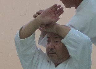 ②振りかぶって左手で受けの同名側の手首を掴んで手背を額に着ける(陰の陰)。