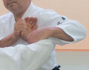 ③右手で受けの小指球を包み右母指は受けの手背に当てて包み・受けの母指球は取りの左胸に密着。画像で、左手は受けの前腕屈側(受けの手が外巡りとなっているので)手背側から四方投げの持ち方近似で伸展して行く所で取りの脇は開いたまま。取りの手関節が完全に伸展したら取りの手背・手首・肘の間が一直線となり、そのまま手関節を曲げないで左膝腰に軸を移しながら振子運動で脇が閉じて行くと・受けの手関節と肘関節はますます屈曲して取りの胸との間で畳まれて行く。二教固め裏