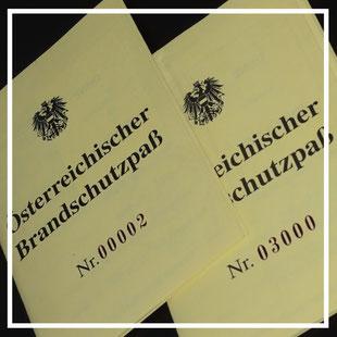 Abbildung von 2 Stk. Österreichischer Brandschutzpässe (gelb, mit einem schwarzen Bundesadler oben sowie der Bezeichnung Brandschutzpass und den Nummern 00002 und 03000)