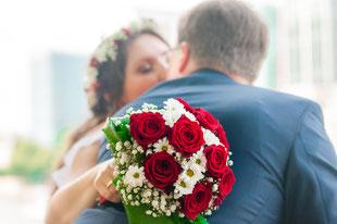 Brautstrauß und sich küssendes Brautpaar