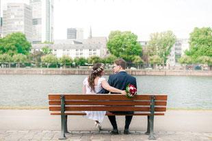 Brautpaar auf der Sitzbank mit Blick auf den Main und die Metropole