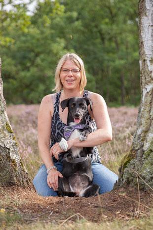 Hundetrainerin Rebecca mit ihrem eigenen Hund auf einer Wiese neben einem Baum