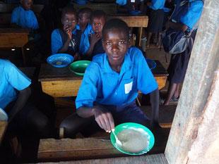 給食中のOkot。午前の給食はトウモロコシの粉のおかゆ。