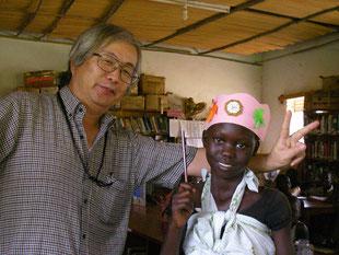 女の子を連れてきたLa賞の紙冠や鉛筆を授け祝福するGum氏。背中の大きな赤ちゃんは重いけど、笑みのこぼれる受賞者です。